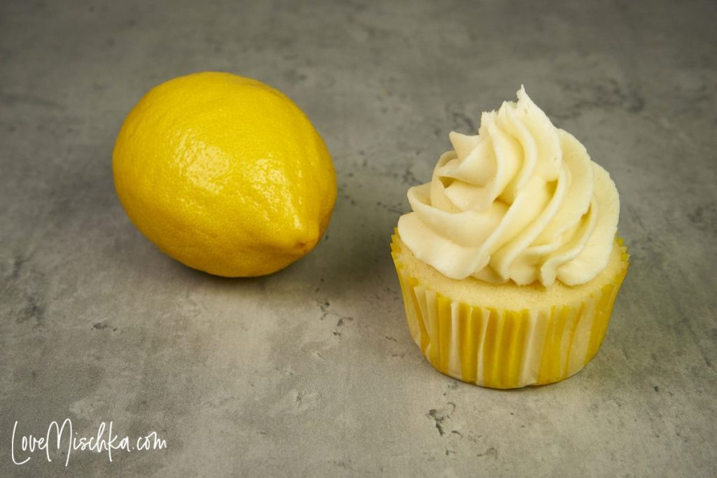 One Lemon Cupcake with Swirled Vanilla Buttercream next to a Lemon on the same size.